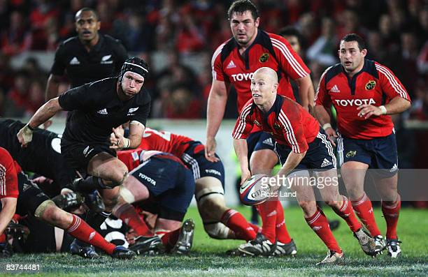 Peter Stringer of Munster clears the ball from the back of a ruck under pressure from Scott Waldrom during the Munster V New Zealand All Blacks rugby...