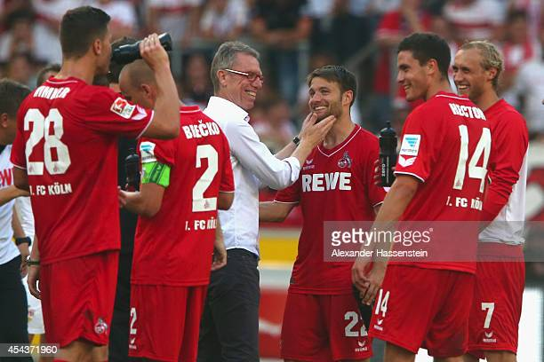 Peter Stroeger head coach of Koeln celebrates with his player Daniel Halfar and other after winning the Bundesliga match between VfB Stuttgart and 1...