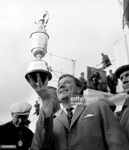 Peter Thomson of Australia holds the claret jug trophy aloft after winning the Open for the fifth time
