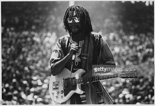 Peter Tosh Holding a Microphone and Guitar
