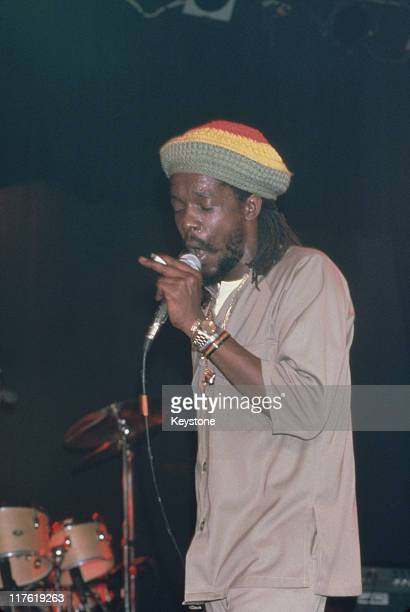 Peter Tosh Jamaican reggae musician and singer singing into a microphone during a live concert performance circa 1985 Tosh was a member of the band...
