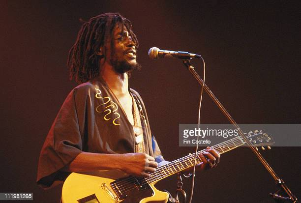 Peter Tosh Jamaican reggae musician playing the guitar while singing into a microphone during a concert circa 1978