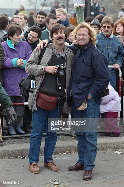 Peter Turnley poses with a fellow photojournalist at the opening of the Berlin Wall