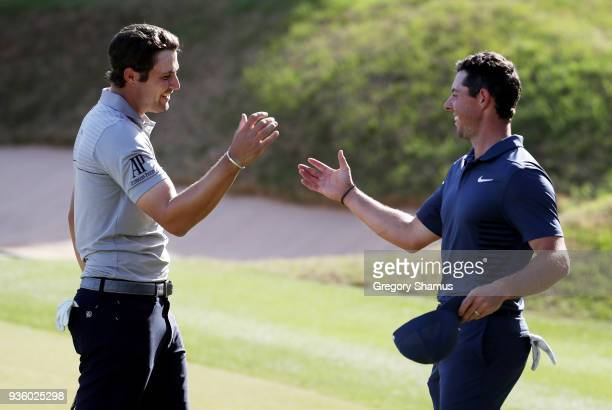 Peter Uihlein of the United States shakes hands with Rory McIlroy of Northern Ireland after defeating him 21 on the 17th green during the first round...