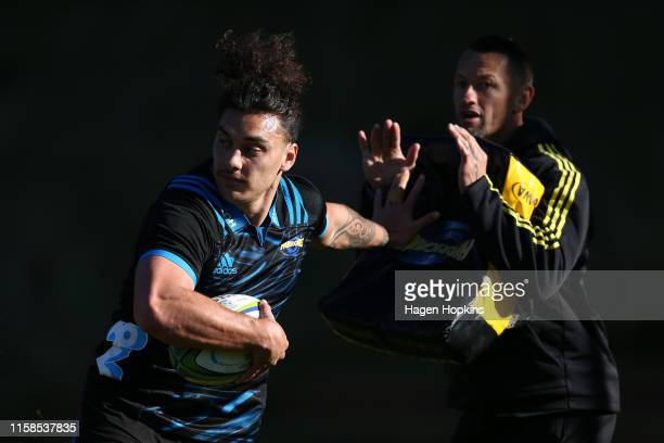 Peter Umaga-Jensen fends assistant coach Carlos Spencer during a Hurricanes Super Rugby training session at Rugby League Park on June 27, 2019 in...