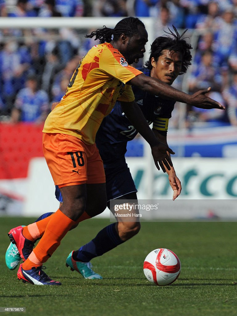 Peter Utaka #18 of Shimizu S-Pulse (L) and Yuji Nakazawa #22 of Yokohama F.Marinos compete for the ball during the J.League Yamazaki Nabisco Cup match between Yokohama F.Marinos and Shimizu S-Pulse at Nippatsu Mitsuzawa Stadium on March 28, 2015 in Yokohama, Kanagawa, Japan.