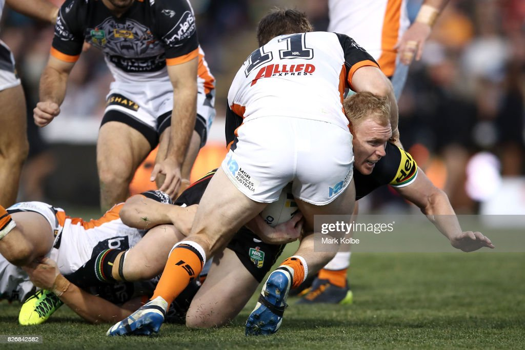 Peter Wallace of the Panthers is tackled by Chris Lawrence of the Tigers during the round 22 NRL match between the Penrith Panthers and the Wests Tigers at Pepper Stadium on August 6, 2017 in Sydney, Australia.