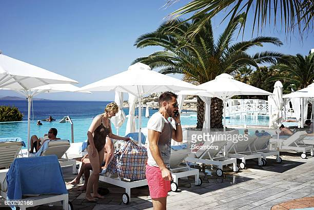 Peter Ward cofounder of the International Conclave of Entrepreneurs center answers a phone call beside the pool at the Saint John Hotel during the...