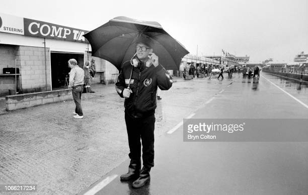 Peter Warr the manager of the Lotus Formula One team stands in the pit lane as his drivers compete in the qualifying session for the 1985 British...
