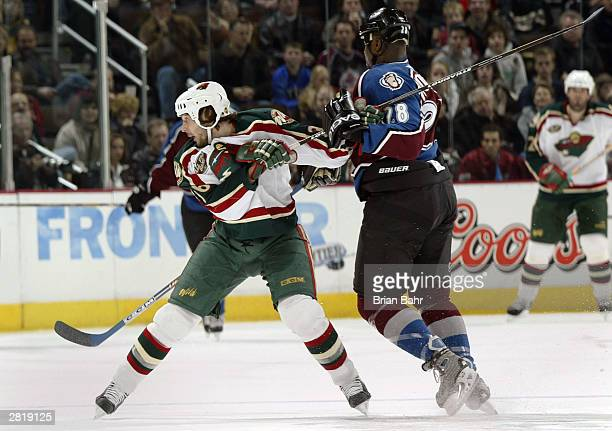 Peter Worrell of the Colorado Avalanche gets caught holding the stick of Christoph Brandner of the Minnesota Wild resulting in a power play goal for...