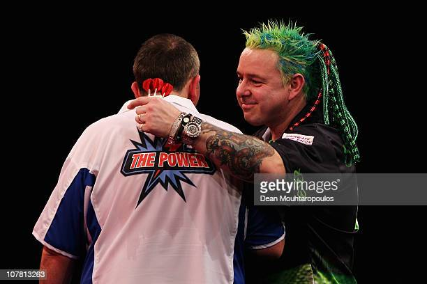 Peter Wright of England and Phil 'The Power' Taylor of England embrace after their match on day 11 in the 2011 Ladbrokescom World Darts Championship...