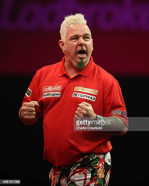 Peter Wright of England celebrates winning a set during his second round match against Per Laursen of Denmark during the Ladbrokescom World Darts...