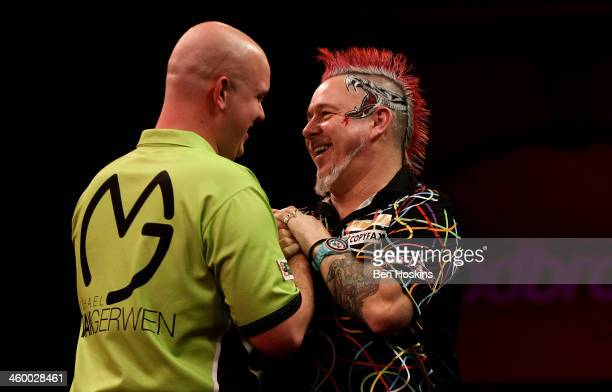 Peter Wright of Scotland congratulates Michael van Gerwen of The Netherlands during the final of the Ladbrokescom World Darts Championships at...