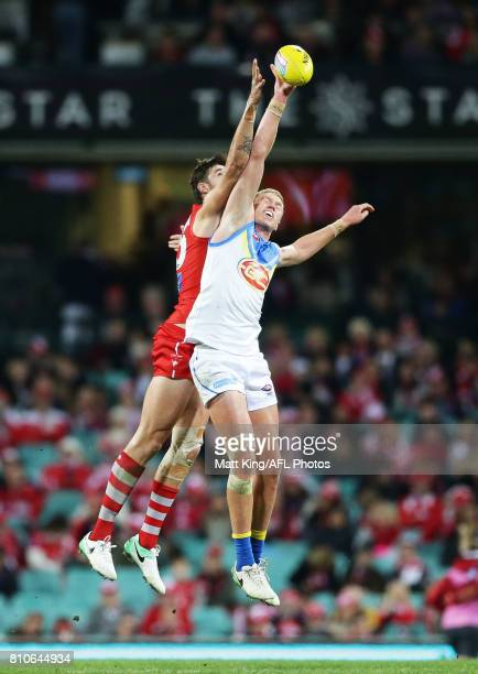 Peter Wright of the Suns is challenged by Sam Naismith of the Swans during the round 16 AFL match between the Sydney Swans and the Gold Coast Suns at...