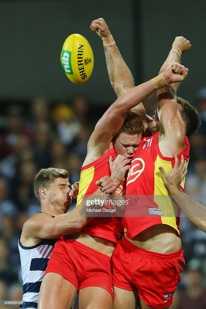 Peter Wright (C) of the Suns is sandwiched when competing for the ball during the round six AFL match between the Geelong Cats and the Gold Coast Suns at Simonds Stadium on April 30, 2016 in Geelong, Australia.