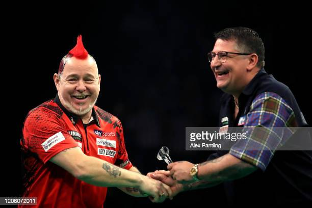 Peter Wright shakes hands with Gary Anderson before their match during day two of the Unibet Premier League at Motorpoint Arena on February 13 2020...