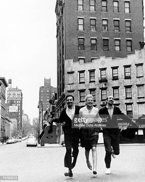 Peter Yarrow Mary Travers and Paul Stookey of the folk group Peter Paul Mary run down the street in circa 1965 in New York City New York