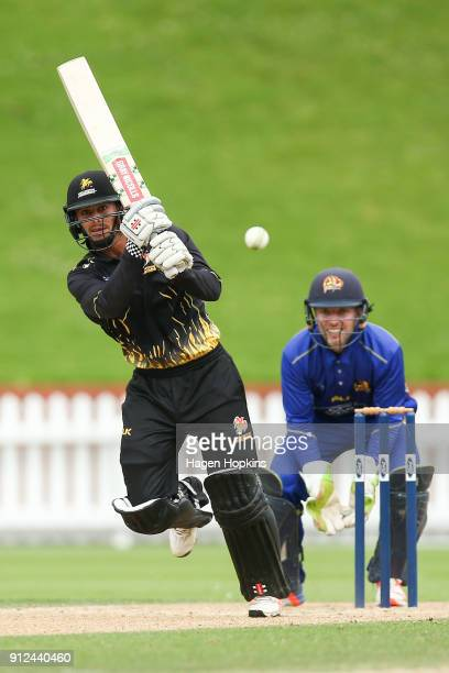 Peter Younghusband of the Firebirds bats while Derek de Boorder of the Volts looks on during the Ford Trophy match between the Wellington Firebirds...