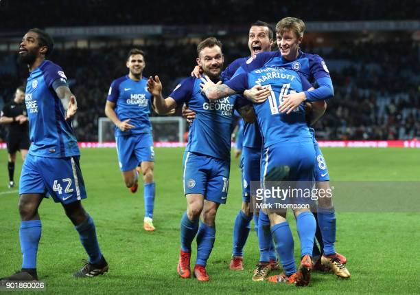 Peterborough players including Steven Taylor celebrate after the The Emirates FA Cup Third Round match between Aston Villa and Peterborough United at...