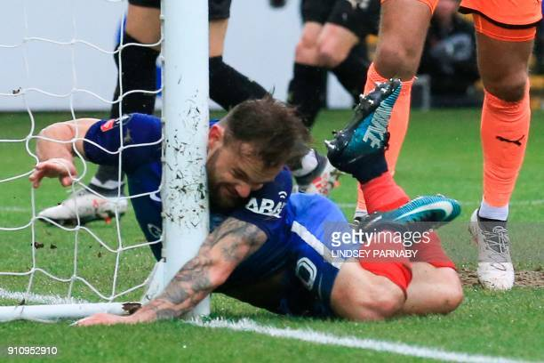 Peterborough United's English midfielder Danny Lloyd slides into the goal post as he tries to meet a cross during the English FA Cup fourth round...