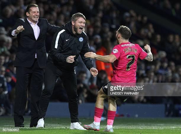 Peterborough United's English midfielder Jon Taylor celebrates scoring his team's second goal with Peterborough United's English manager Graham...