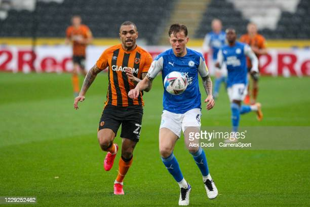 Peterborough United's Frankie Kent shields the ball from Hull City's Josh Magennis during the Sky Bet League One match between Hull City and...