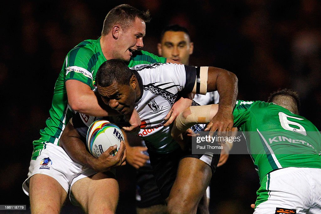 Petero Civoniceva of Fiji is tackled by Ireland's Ben Currie (L) and James Mendeika during the Rugby League World Cup Group A match between Fiji and Ireland at Spotland Stadium on October 28, 2013 in Rochdale, England.
