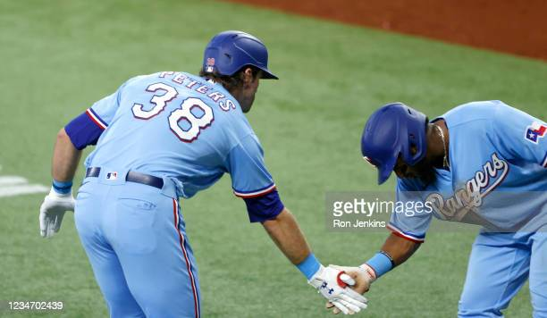 Peters of the Texas Rangers celebrates with teammate Yonny Hernandez after hitting a two-run home run against the Oakland Athletics during the fifth...