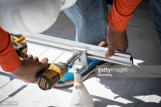 A PetersenDean Inc employee fastens a rail to hold a solar panel during installation on the roof of a home in Lafayette California US on Tuesday May...
