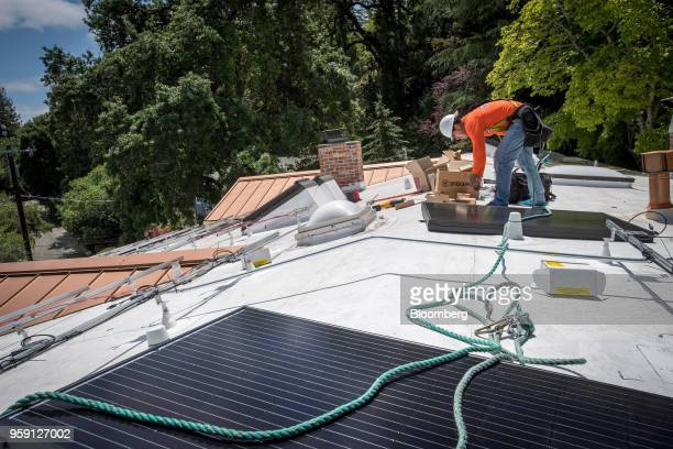A PetersenDean Inc employee installs solar panels on the roof of a home in Lafayette California US on Tuesday May 15 2018 California became the first...