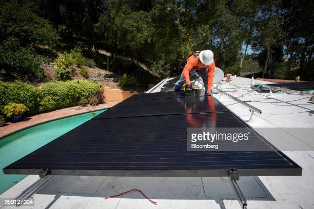 A PetersenDean Inc employee installs solar panels on the roof of a home in Lafayette California became the first state in the US to require solar...