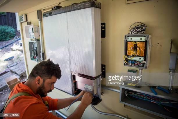A PetersenDean Inc employee installs wiring for a LG Electronics Inc solar battery on a home in Lafayette California US on Tuesday May 15 2018...