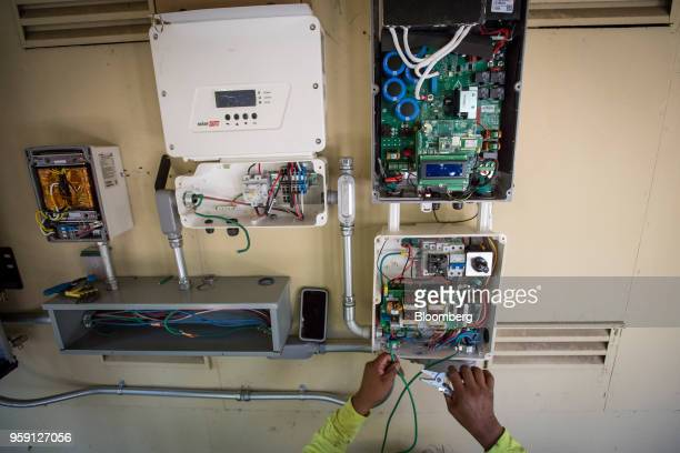 A PetersenDean Inc employee installs wiring for a solar inverter on a home in Lafayette California US on Tuesday May 15 2018 California became the...