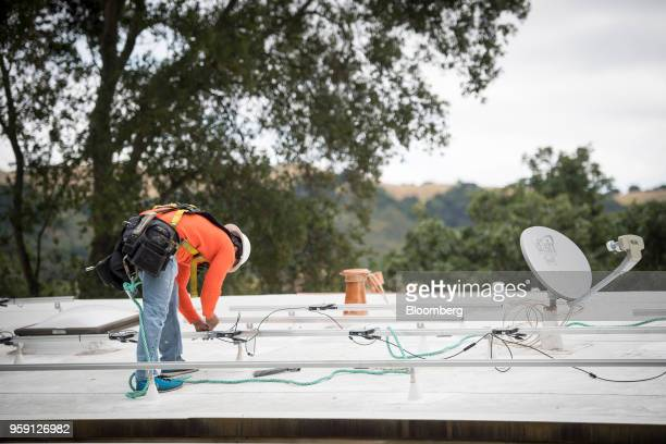 A PetersenDean Inc employee installs wiring for solar panels on the roof of a home in Lafayette California US on Tuesday May 15 2018 California...