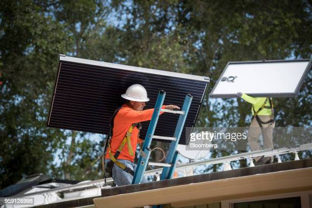 PetersenDean Inc employees carry solar panels onto the roof of a home in Lafayette California US on Tuesday May 15 2018 California became the first...