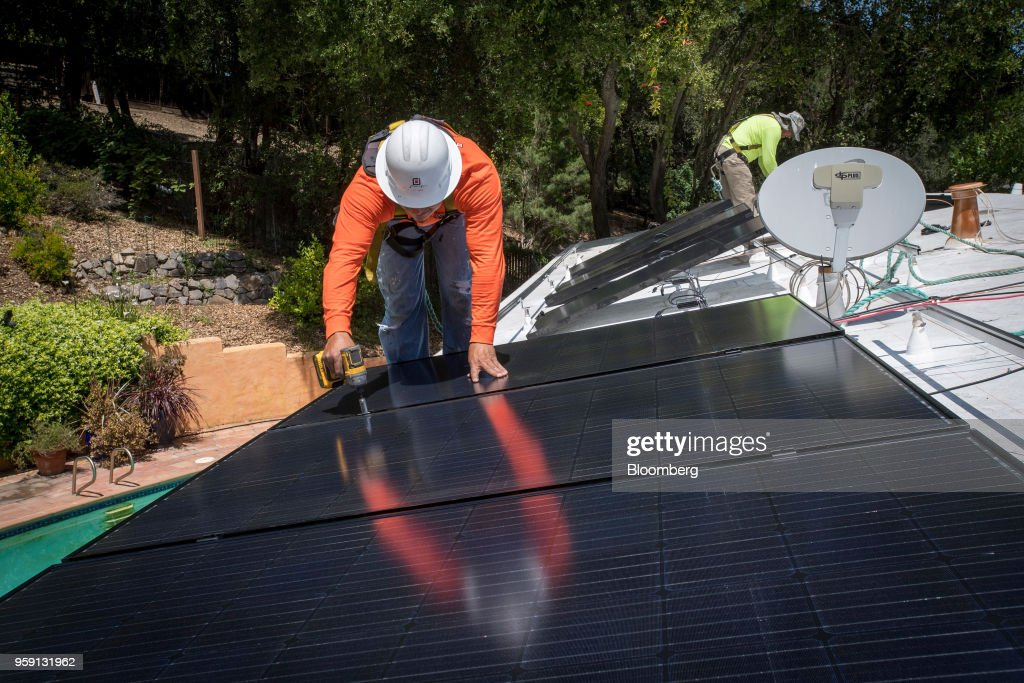 PetersenDean Inc. employees install solar panels on the roof of a home in Lafayette, California, U.S., on Tuesday, May 15, 2018. California became the first state in the U.S. to require solar panels on almost all new homes. Most new units built after Jan. 1, 2020, will be required to include solar systems as part of the standards adopted by the California Energy Commission. Photographer: David Paul Morris/Bloomberg via Getty Images