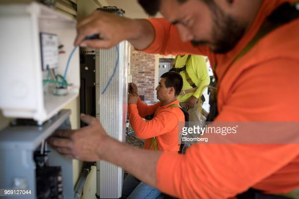 PetersenDean Inc employees install wiring for solar power on a home in Lafayette California US on Tuesday May 15 2018 California became the first...