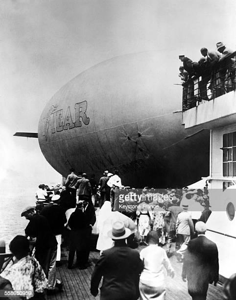 Petit ballon dirigeable atterrissant sur le pont d'un paquebot pour prendre des passagers et les conduire à destination plus rapidement circa 1930