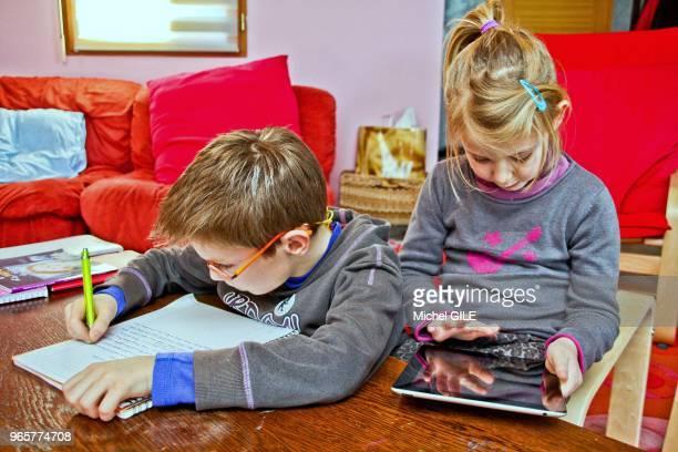 Petit garcon de 9 ans écrivant sur un cahier et petite fille de 6 ans jouant sur sa tablette numérique.