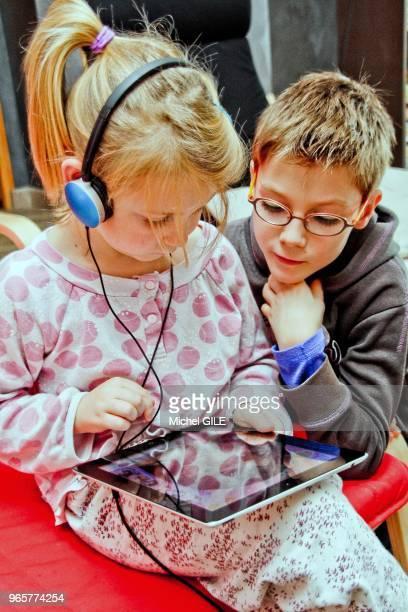 Petit garcon de 9 ans regardant sa petite soeur de six ans jouer avec sa tablette numérique en ecoutant de la musique.