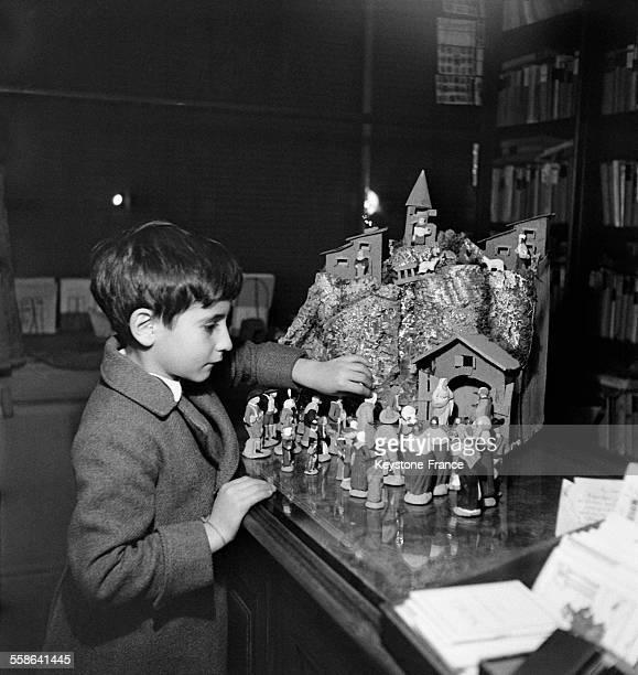 Petit garçon devant une crèche de Noël remplie de santons à Vichy France le 16 décembre 1942