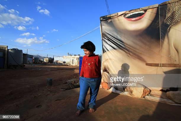 Petit garçon, prénommé Ramadan, originaire de Deir ez-Zor , qui a fui avec sa famille le conflit syrien, devant une tente de refugiés construite avec...