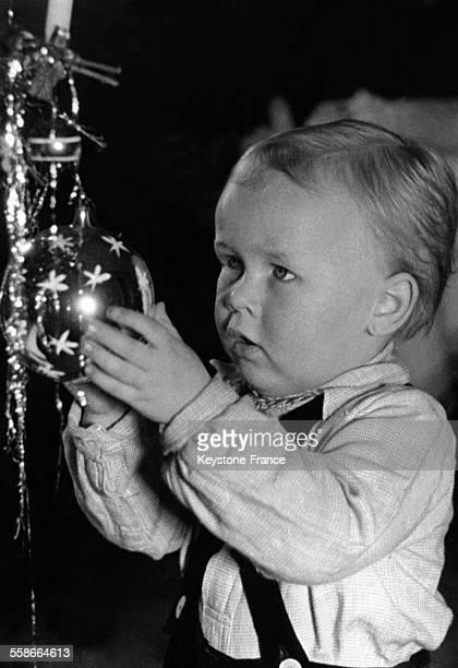 Petit garçon regardant une boule de Noël en Allemagne le 16 décembre 1938
