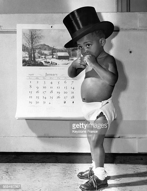 Petit garçon vêtu d'une coucheculotte et portant un chapeau hautdeforme pose devant le calendrier pour la nouvelle année à l'hôpital de New York City...