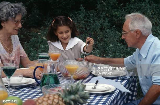 Petite fille avec ses grands parents lors d'un repas de famille dans un jardin à Créteil en 1995 dans le ValdeMarne France