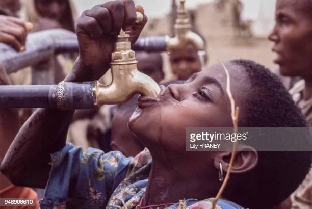 Petite fille buvant de l'eau au robinet dans le camp de réfugiés à Mekele pendant la famine de 1985 Ethiopie