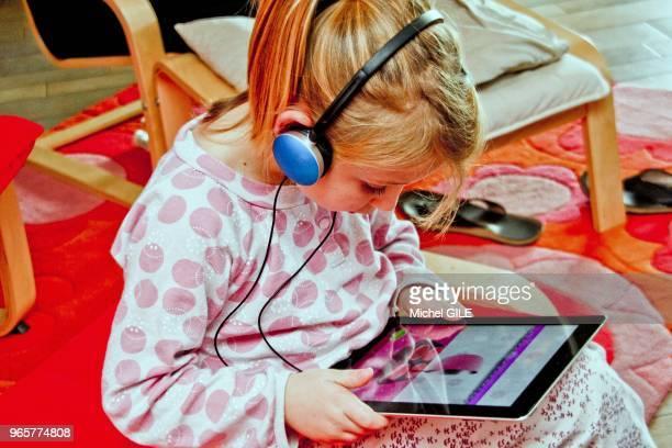 Petite fille de six ans ecoutant de la musique avec un casque et une tablette numérique.