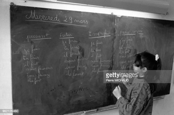 Petite fille faisant de la conjugaison au tableau dans une école primaire à Concarneau dans le Finistère France