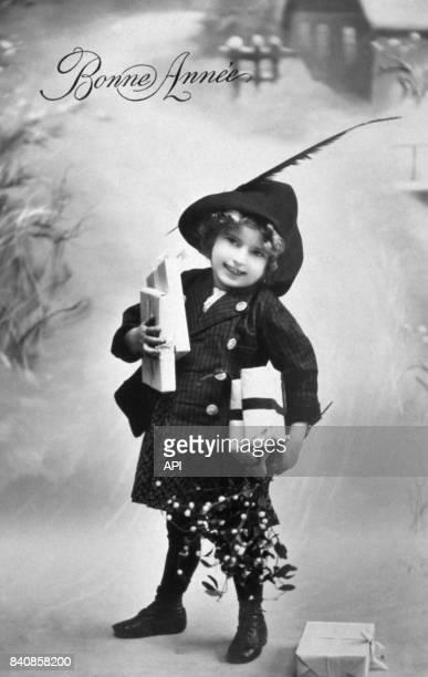 Petite fille posant avec des cadeaux de Noël pour une carte de voeux en 1910