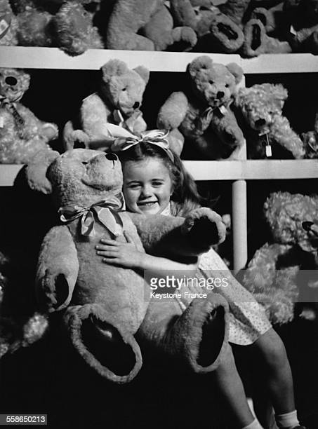 Petite fille tenant affectueusement dans ses bras un gros ours en peluche, dans un rayon du magasin Harrods, a Londres, Royaume-Uni.